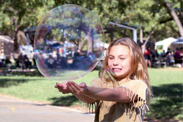 Corallyn Moss catches a bubble during the Indigenous Peoples Days celebration at Sycamore Ranch Park in Browns Valley Sunday.