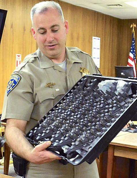 California Highway Patrol Officer Greg Tassone gives students a close-up look at a spike strip, often used to flatten the tires of fleeng a car, during Friday's Law Day program at the Nevada County Courthouse.