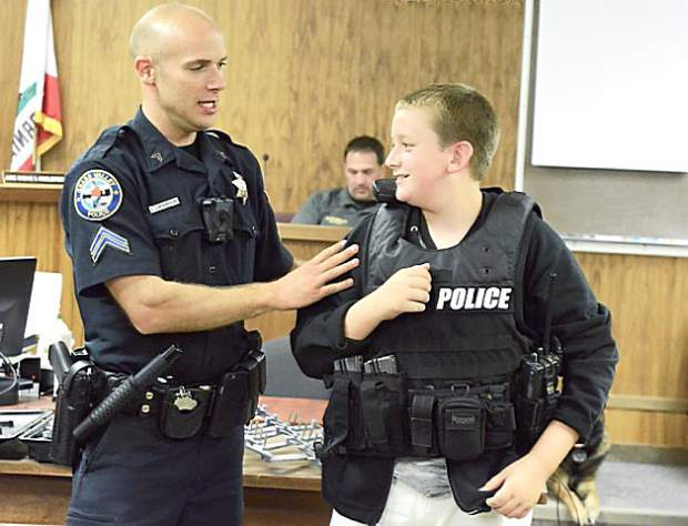 Grass Valley Police Corporal Zack LaFerriere, left, geats Seven Hills School fifth-grader Ben Herrgesell geared up during the annual Law Day program at the Nevada County Courthouse. About 700 students participate in the event each year.