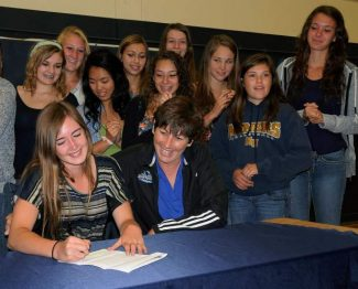 Nevada Union's Nicole Lierly, left, signs her National Letter of Intent to attend California State University, San Marcos, as her future coach Sheri Jennum, right, looks on.