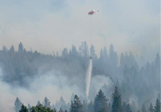 Sac Metro's air support helicopter drops roughly 350 gallons of water on top of a hotspot at the Lowell Fire on Monday.