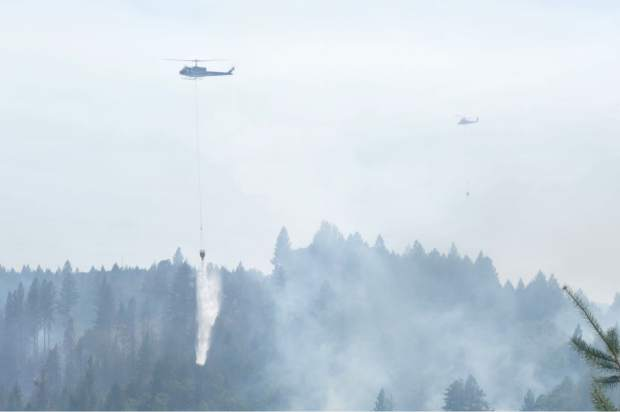 An air support helicopter drops roughly 350 gallons of water on top of a hotspot at the Lowell Fire on Monday.