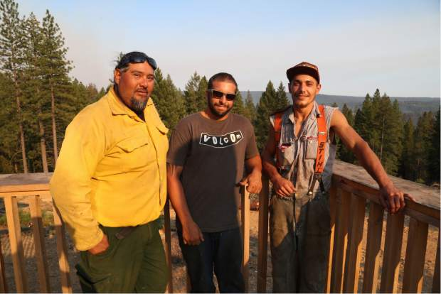 California firefighter, Ray Torres, and local home owners after saving another home at the Lowell Fire in Nevada County on Monday.
