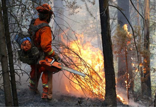A Cal Fire firefighter works the Lowell Fire.