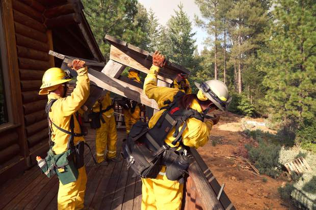 Nevada County firefighters protect a home off Chalk Bluff Rd from the Lowell Fire on Saturday.