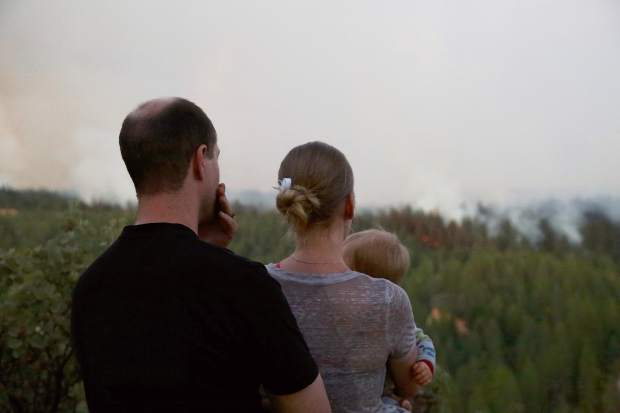 Local home owners watch the Lowell Fire burn near their property on Saturday.