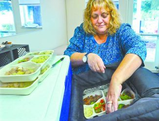 Jacquie O'Hare, a volunteer for the Meals on Wheels, checks a meal prior to delivery to western Nevada County seniors in this 2012 photograph.