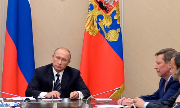ALTERNATIVE CROP OF MOSB107 Russian President Vladimir Putin, left, holds a meeting with senior government officials at the Novo-Ogaryovo residence outside Moscow, Russia on Wednesday, Sept. 30, 2015. Russian military jets carried out airstrikes against the Islamic State group in Syria on Wednesday for the first time, after President Vladimir Putin received parliamentary approval to send Russian troops to Syria. Sergei Ivanov, head of presidential staff sits at right. (Alexei Nikolsky/RIA Novosti, Kremlin Pool Photo via AP)
