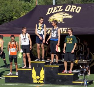 Garrett Migliozzi of Nevada Union stands on top of the posium after winning a gold medal for the boys varsity track and field team in the 1500 meter race at the Del Oro Invitational on Friday.