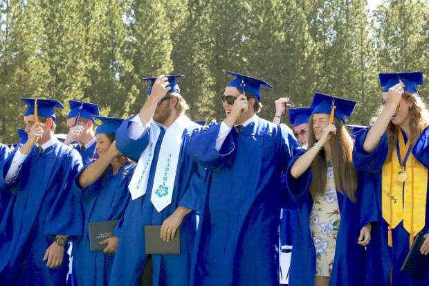 Nevada Union graduates move their tassel after receiving their diplomas at Hooper Stadium Saturday morning.