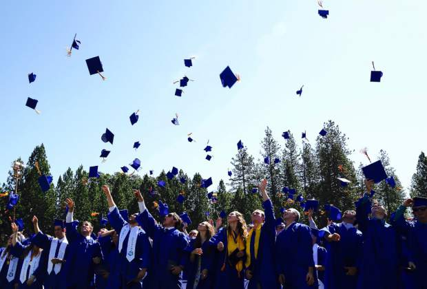 Nevada Union graduates throw their hats after receiving their diploma at Hooper Stadium Saturday morning.
