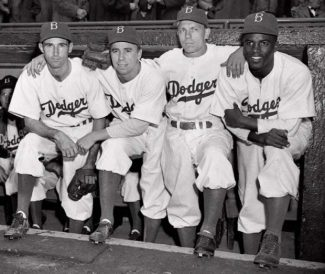 """FILE - In this April 15, 1947 file photo,  from left, Brooklyn Dodgers baseball players John Jorgensen, Pee Wee Reese, Ed Stanky and Jackie Robinson pose at Ebbets Field in New York. Kansas City's Negro Leagues Baseball Museum is hosting an advance screening of an upcoming movie about Robinson, who broke major league baseball's color barrier. Thomas Butch of the financial firm Waddell and Reed announced Wednesday, March 20, 2013 that actors Harrison Ford and Andre Holland will be among those appearing at an April 11 screening of """"42.""""   (AP Photo, File)"""