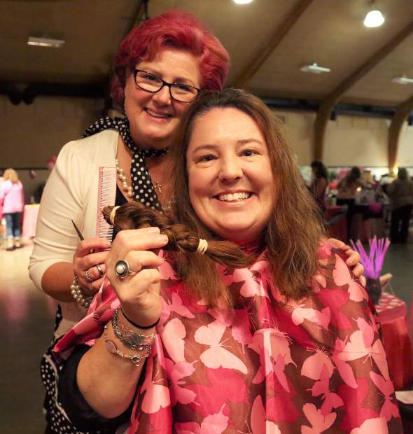 Jennifer Anderson of Nevada City Chocolate Shop donates her hair to Pony Up, a organization that donates wigs to cancer patients. Tania Fisher of Image by Design Hair and Makeup Studio cuts hair during Paint the Town Pink at the Nevada County Fairgrounds Thursday evening.