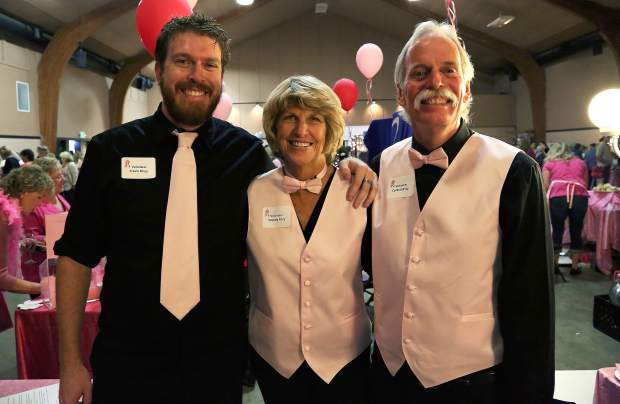 Travis, left, Wendy and Corbett Riley offer bar service during Paint the Town Pink at the Nevada County Fairgrounds Thursday evening.