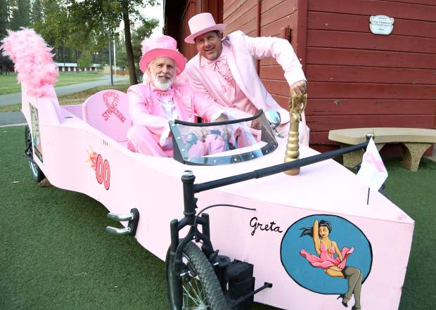 Ed Arnott, left, and Mel bring their soapbox car, Greta, to Paint the Town Pink at the Nevada County Fairgrounds Thursday evening.