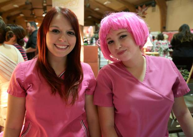 Cassandra Goldstein, left, and Hannah Glazebrook volunteer during Paint the Town Pink at the Nevada County Fairgrounds Thursday evening.