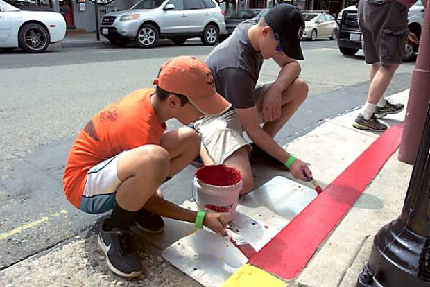 Anthony Devine and Logan Blue, of Boy Scouts Troop 855, paint a red zone on Mill Street. Volunteers painted buildings, red and green zones on sidewalks and light posts in downtown Grass Valley during the