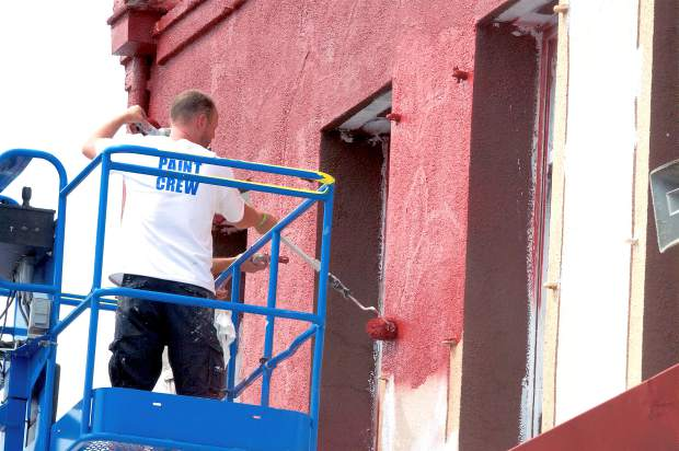 Painters paint the top half of a building on Mill Street using a sprayer and rollers. Volunteers painted buildings, red and green zones on sidewalks and light posts in downtown Grass Valley during the