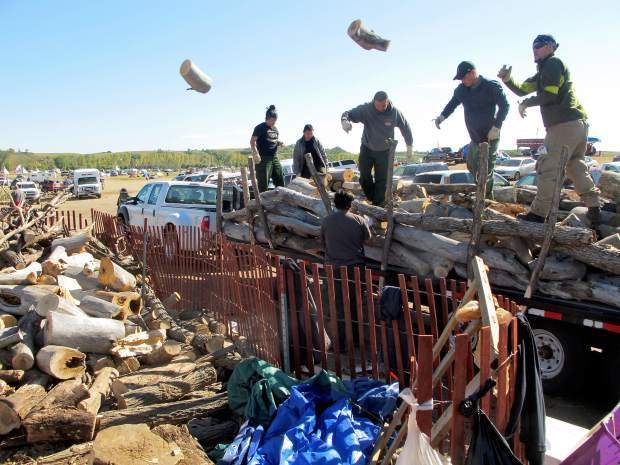 In this Wednesday, Sept. 14, 2016, photo, volunteers toss logs at an oil pipeline protest encampment near the Standing Rock Sioux Reservation in southern North Dakota. The logs will be used to cook meals for the thousands of people who have come to the area to fight the $3.8 billion Dakota Access pipeline. (AP Photo/James MacPherson).