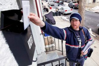 FILE - In this Tuesday, March 2, 2010 file photo, letter carrier Kevin Pownall delivers mail in Philadelphia. The financially struggling U.S. Postal Service announced on Wednesday, Feb. 6, 2013 it will stop delivering mail on Saturdays but continue to deliver packages six days a week under a plan aimed at saving about $2 billion a year.  (AP Photo/Matt Rourke, File)