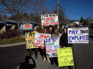 Stephanie Lee (far right) gathered her friends and family on Friday to protest what she claims is unfair treatment of her husband and father, both of whom work at the 10 Minute Oil Change and Carwash in Grass Valley.