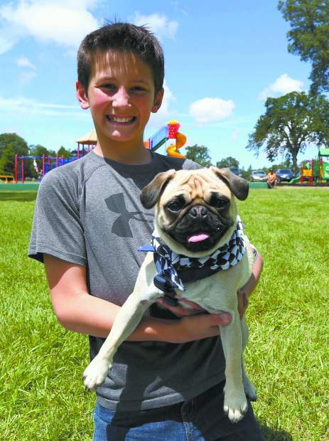 Maddox Graves and McSquizzy enjoy the Pug Sunday Pug Races at Western Gateway Park in Penn Valley Sunday morning.