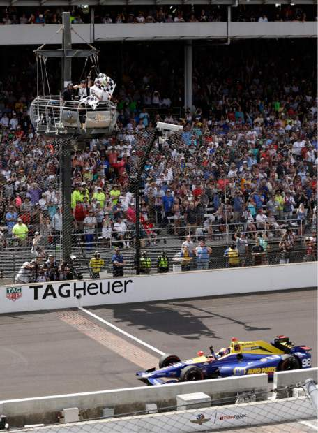 Alexander Rossi takes the checkers flags as he crosses the finish line to win the 100th running of the Indianapolis 500 auto race at Indianapolis Motor Speedway in Indianapolis, Sunday.