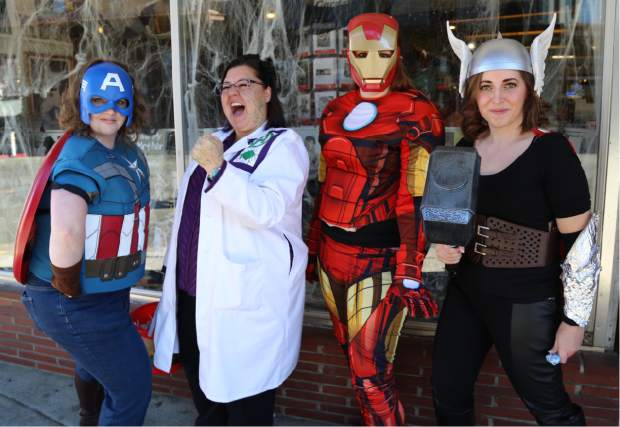 The Book Seller employees distribute candy during Safe Trick or Treat in downtown Grass Valley Friday.