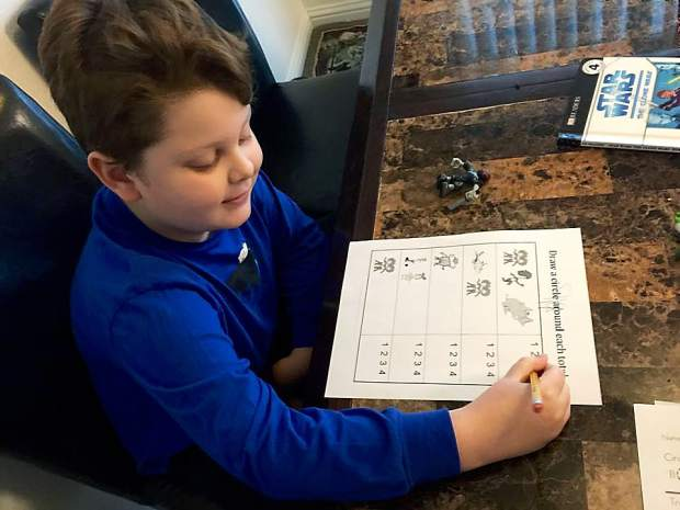 Eight-year-old Silas Hurd completes school work in his family's Penn Valley home. For the past several months, Hurd's family has been using medical marijuana to control Silas' severe form of epilepsy.