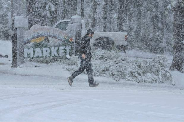 A person walks in the snowstorm on Highway 20 to Harmony Ridge Market, Tuesday morning.