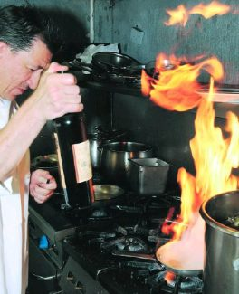 John HartRobert Perez, owner/chef of Citronee on Broad Street in Nevada City, puts brandy in a pan for a cooked fruit dish.