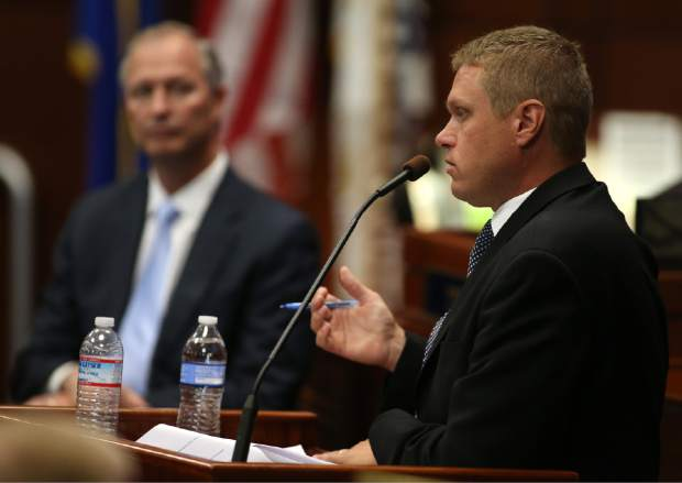 Nevada Tax Director Chris Nielsen, right, answers questions on the Senate floor during the second day of a special session at the Nevada Legislature, in Carson City, Nev., on Thursday, Sept. 11, 2014. Lawmakers are considering a complex deal to bring Tesla Motors to Nevada. Steve Hill, with the Governor's Office of Economic Development is at left. (AP Photo/Cathleen Allison)