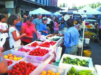 Photo courtesy of Julia Jordan. Customers and passersby search for produce at the Thursday Night Market in downtown Grass Valley in 2012. Grass Valley Downtown Association is seeking a new Growers Manager for the agriculture section of the market.