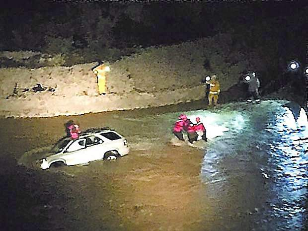Firefghters and members of the swift water rescue team rescue two people trapped in a vehicle in Greenhorn Creek Jan. 17.