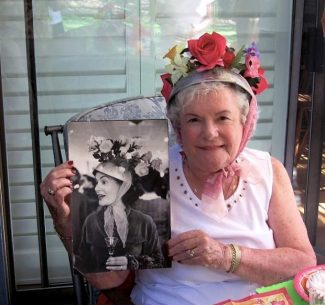 Jean Humburg models a hat at the Mad Hatter's Party sponsored by the VJ chapter of Philanthropic Educational Organization (PEO). She is holding a Life magazine photo of her wearing the same colander at a 1956 Officer's Wives' Crazy Hat Party at Patrick Air Force Base in Cape Canaveral.