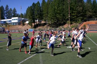 """Last Sunday, the Nevada Union High School varsity football team hosted their first """"Future Miners Youth Clinic"""" at Hooper Stadium. More than 50 future miners from Grass valley and Nevada City participated in the clinic. The day featured speed and agility drills as well as football skills taught by NU team members. Above, Future Miners warm up for drills."""