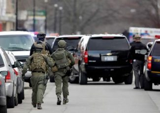 Police walk along Main Street in Herkimer, N.Y., as they search for a suspect in two shootings that killed four and injured at least two on, Wednesday, March 13, 2013. Multiple gunshots rang out as police on foot and in a helicopter swarmed two upstate New York villages in search of a 64-year-old man they say opened fire at a car wash and a barbershop Wednesday morning, killing four people and wounding at least two others.  (AP Photo/Mike Groll)