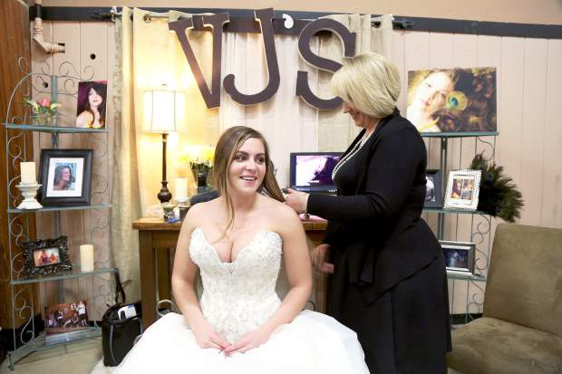 Lucy Brindley styles Briana Goode's hair during the Wedding Fair at the Nevada County Fairgrounds Sunday afternoon.