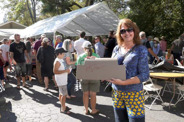 Mary Anne Davis has Alexander Rossi sign her son's glove box during the 25th annual Rotary Duck Race in Nevada City Sunday afternoon.