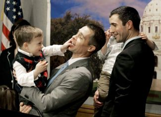 Dr. Paul Melchert, left, gets interrupted by his son, Emmett, as he attempts to address the media while his partner James Zimerman, right, holds Emmett's twin brother, Gabriel, during a news conference Wednesday, Feb. 27, 2013, in St. Paul, Minn. Lawmakers introduced a bill Wednesday to legalize gay marriage in Minnesota. Arguing that such families deserve the same recognition from the state as more traditional ones, sponsors of the gay marriage bill aim to repeal Minnesota's 1997 law that prohibited marriage between couples of the same sex. The bill exempts churches from being forced to perform same-sex weddings. (AP Photo/Jim Mone)