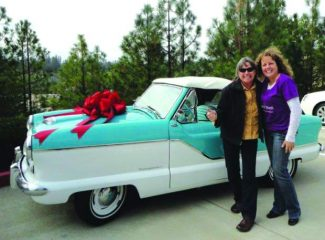 Sculla Conrad, left, a resident of Crockett, Calif., gives a thumbs up on her new ride, a 1959 Nash Metropolitan, which she won in a raffle sponsored by Women of Worth, whose executive director is Sandy Schmidt, right, in this 2011 file photo.