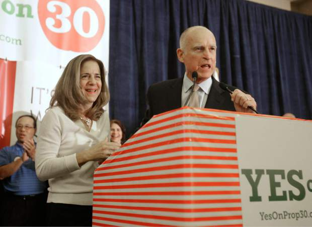 FILE - In this Nov. 6, 2012 file photo, Calif., Gov. Jerry Brown and his wife, Anne Gust Brown thank supporters for their work on his temporary tax hike initiative, Proposition 30, during an election night party in Sacramento, Calif.  Brown called the Legislature into a special session in the summer of 2015 to decide whether to extend the $1 billion tax on health plans or cut services in a $91 billion program that offers care to roughly 1 in 3 Californians.  (AP Photo/Rich Pedroncelli, File)