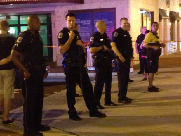 Police stand early Sunday, Oct. 18, 2015, near the site of a shooting late Saturday at ZombiCon that police say killed on person and injured four others in Fort Myers Fla.