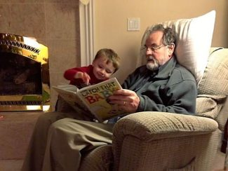 Photo courtesy of Carolyn Anderson. John Zwerver reads to his three-year-old grandson, Peter, Dec. 23, 2012, just before he was taken to the hospital for a brain infection.