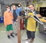 Bike manufacturer Chris Kelly of Kelly Bike Company, right, demonstrates brazing to Seven Hills Middle School student Jeremy Case, left, on Wednesday while teacher Steve Davis, center, films the process. Kelly is spending all this week with Seven Hills students, helping them build a bicycle frame from scratch.