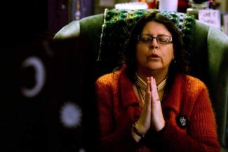 """In a show of solidarity with the Dakota Access oil pipeline protesters in Cannon Ball, ND., the co-owner of Ingress Yugen Audra Hollenbeck, 49, of Flushing, prays on Saturday, Nov. 26, 2016 at Ingress Yugen, a spiritual resource center, in Flint, Mich. """"Some people can say what we did tonight was silly but we know that every action has a reaction,"""" said Derrik Gilliard, 44, of Flint, who co-owns Ingress Yugen. """"If we can show solidarity from many miles away, than maybe other individuals can also have the courage to stand in support of Standing Rock."""" (Callaghan O'Hare/The Flint Journal-MLive.com via AP)"""