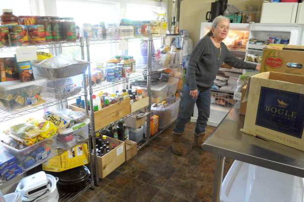 Pauli Halstead, owner of the property where the Streicher House is located, shows off the kitchen that is stocked with food donated by the Nevada County Food Bank, Interfaith Minstries, and other area donors, which is used to make a warm meal each day for area homeless.