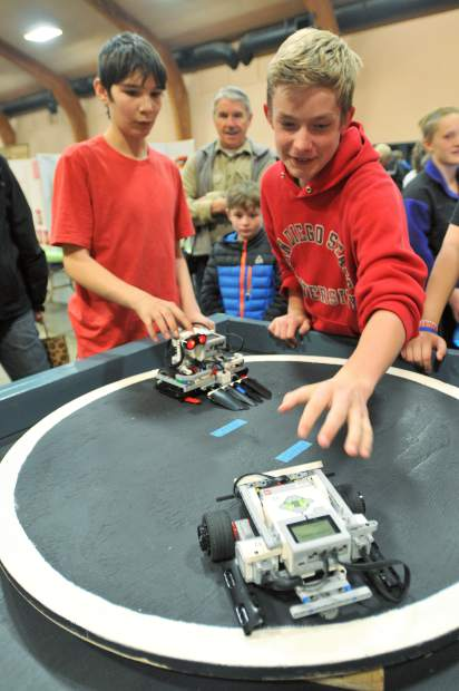 Thirteen year old Union Hill eigth grader Lars Fjeldheim (right) releases his sumo-bot, while twelve year old Union Hill seventh grader Joseph Forest readies to release his sumo-bot. The pre-programed autonomous robots will move around the ring by themselves and try to knock the other one out.
