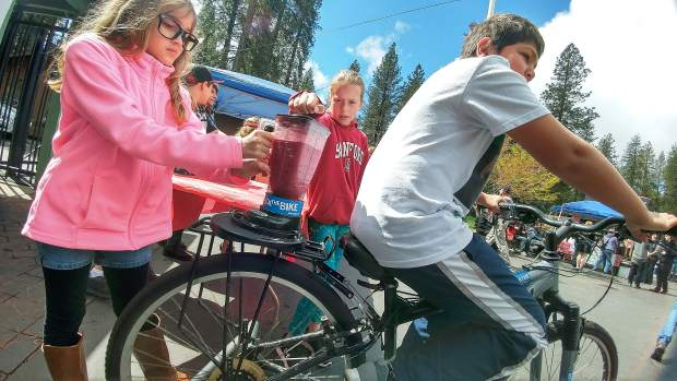 Cottage Hill Elementary's Eddie Kenes pedals away on a smoothie making mountain bike while Deer Creek Elementary's Arianna Drageset and Megan Reveles hold the blender firmly in place at Saturday's STEAM Expo. The finished product was offered for $1 with benefits going to the Healthy Kids Program at Deer Creek Elementary.