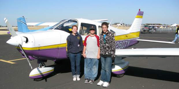 Chrissy Mut, Teylon Golsong and Tristan Golson get their Young Eagles flight from Grass Valley pilot Bill Sommers.